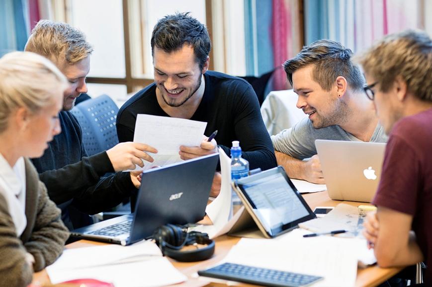 Fem studenter sitter sammen og jobber ved pc-ene. Foto.